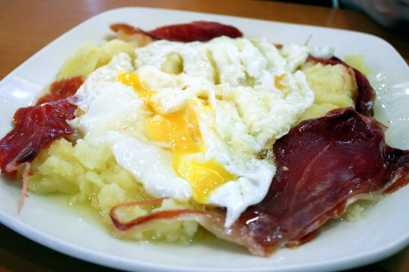 Spanish Egg Dishes: Huevos Rotos are Spanish eggs over potatoes with cured ham.