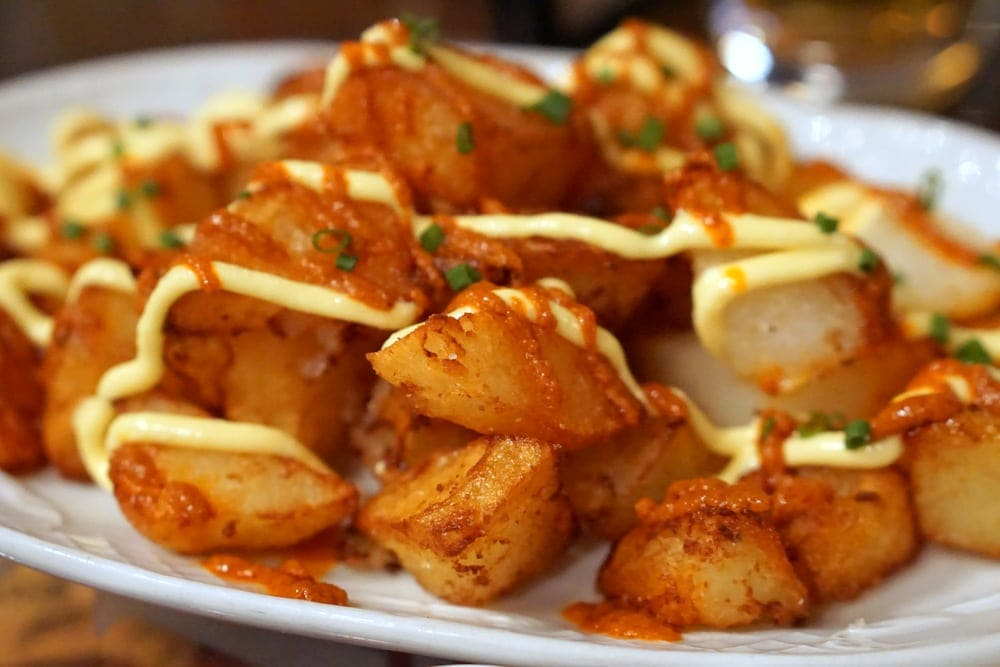Taking a tapas tour in Barcelona. Patatas bravas in Barcelona are a traditional food to share!