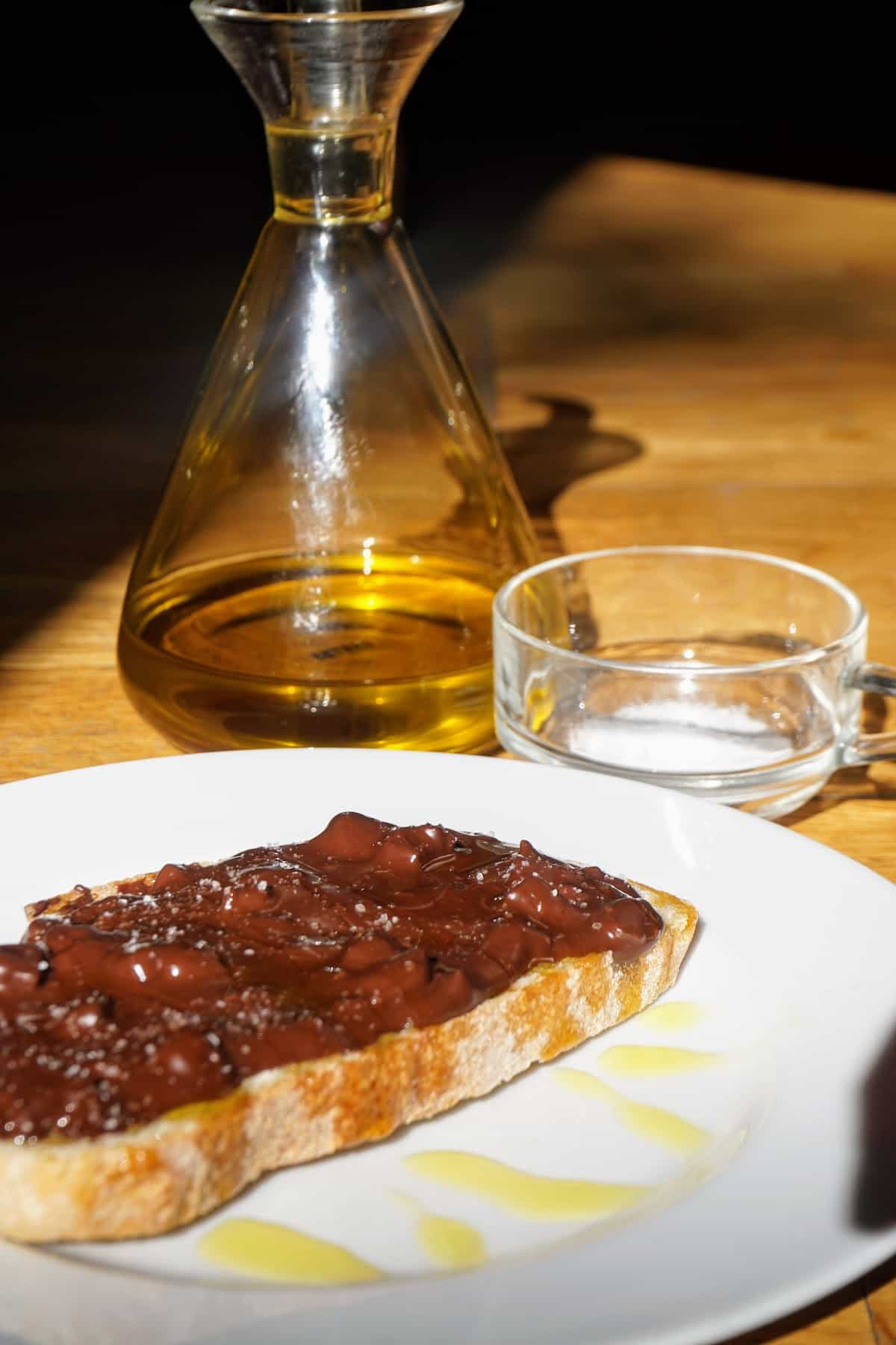 Slice of toasted bread topped with chocolate and olive oil, with containers of olive oil and salt behind the plate.