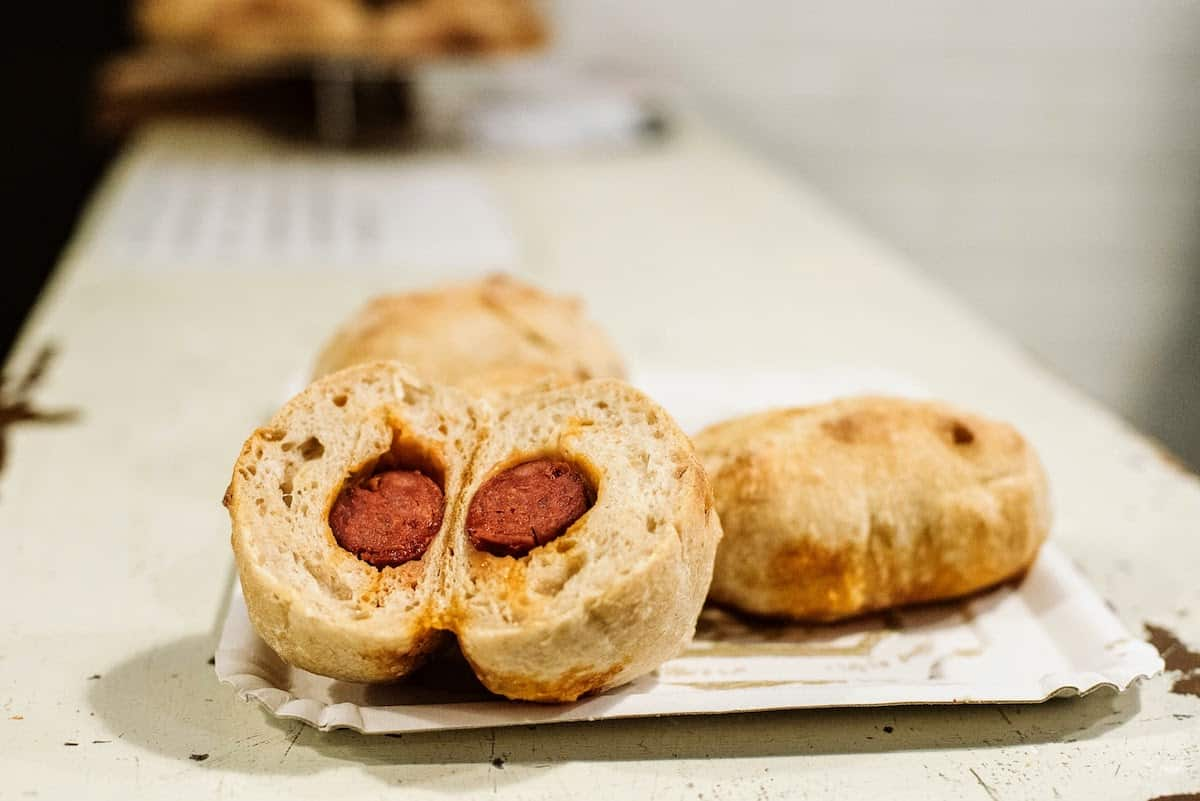 Two bread rolls on a small white plate, one of which has been cut open to reveal the filling of chorizo inside.