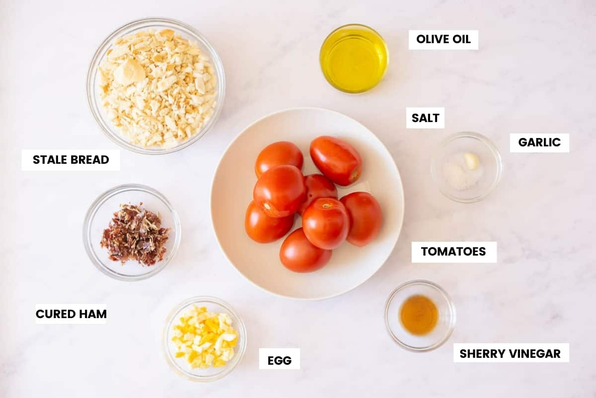Ingredients for salmorejo recipe on a white marble counter. Tomatoes, olive oil, bread, ham, eggs, vinegar and garlic.