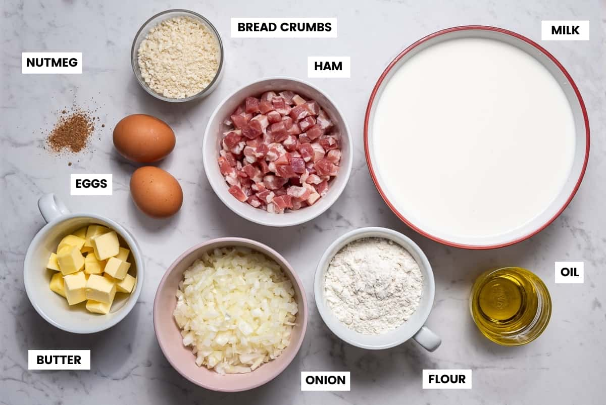 Ingredients to make Spanish ham croquettes laid out on white marble counter.
