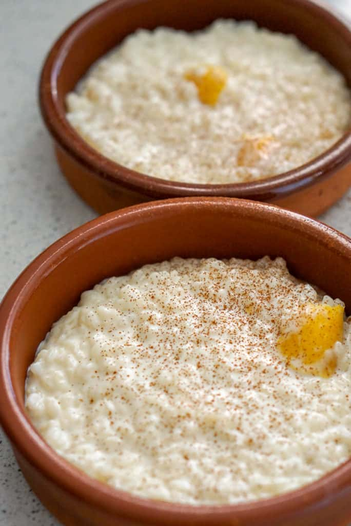 Two servings of arroz con leche in clay bowls.