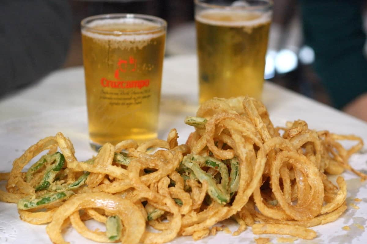 Fried rings of onions and pepper in front of two small glasses of draft beer.