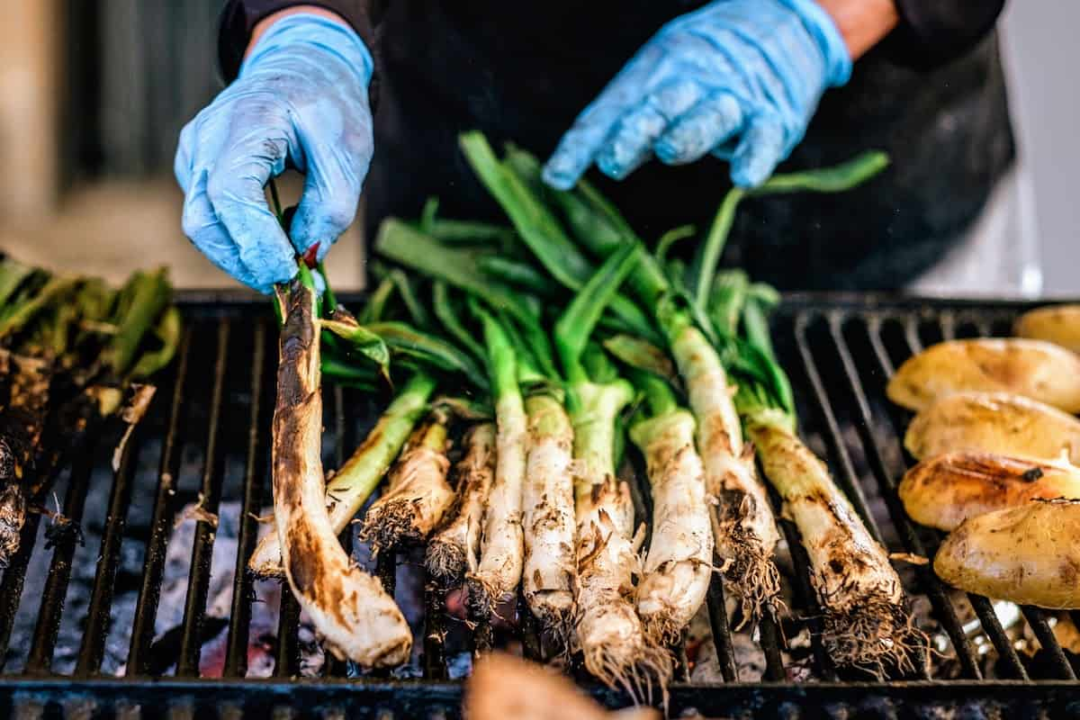 Spring onions with green stalks on a grill.