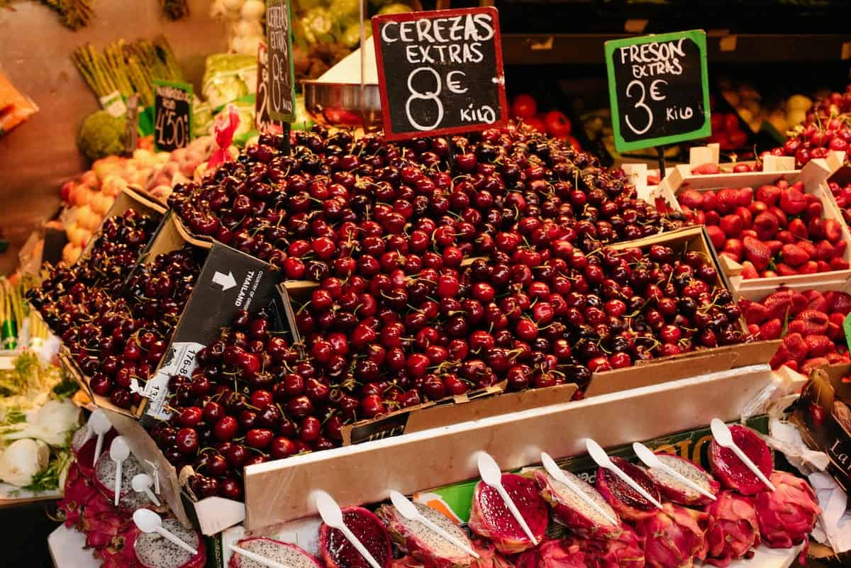 Boxes full of dark red cherries at a market stall.