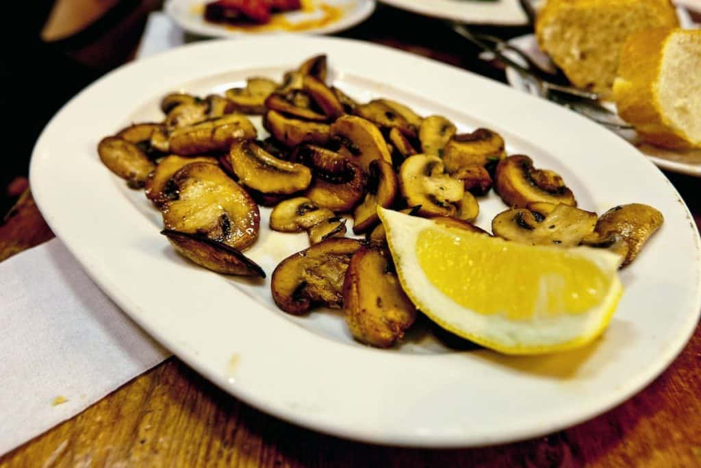 Plate of grilled mushrooms with a lemon wedge.