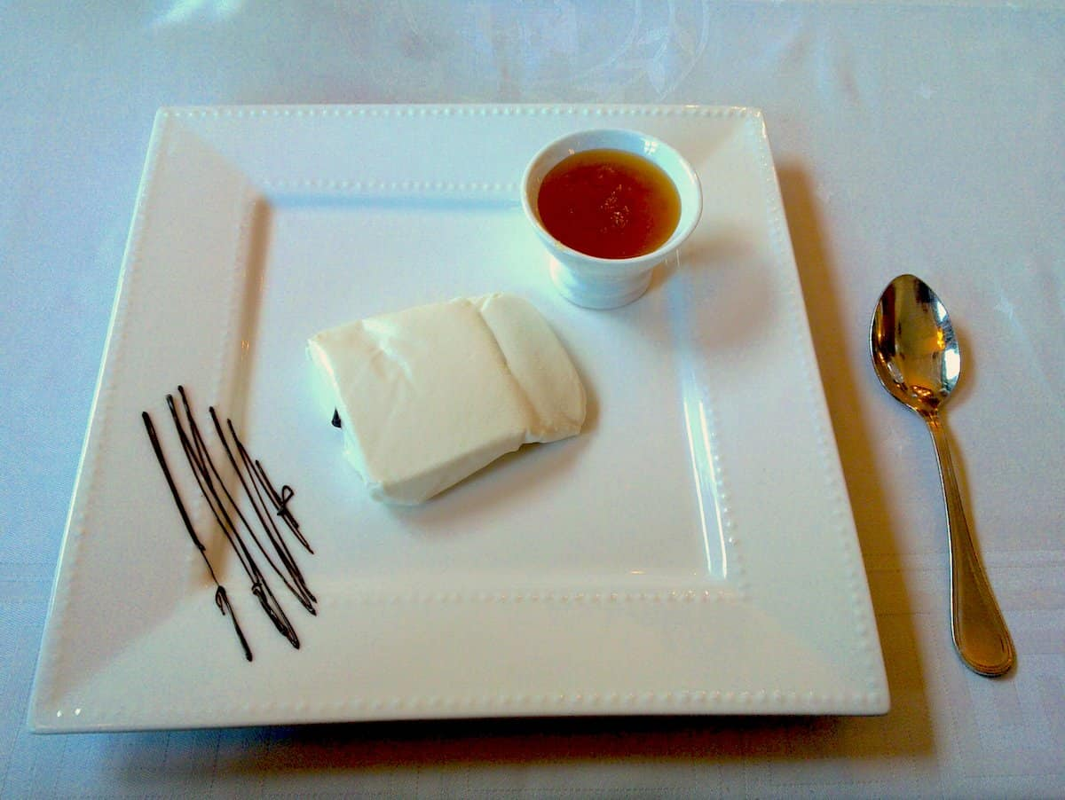 Plate of fresh cheese with a small cup of honey beside it.