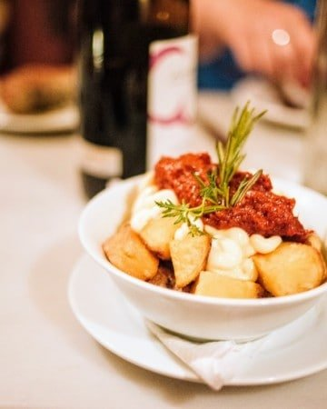 Dish of fried potato chunks topped with garlic mayonnaise and a spicy red sauce and garnished with a sprig of herb.
