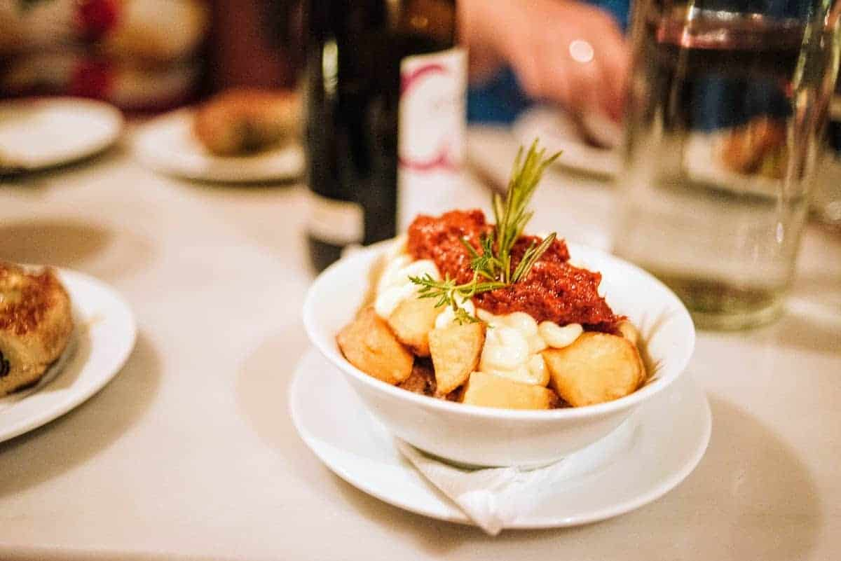 Dish of fried potato chunks topped with garlic mayonnaise and a spicy red sauce and garnished with a sprig of herb, one of Spain's best vegetarian tapas recipes.