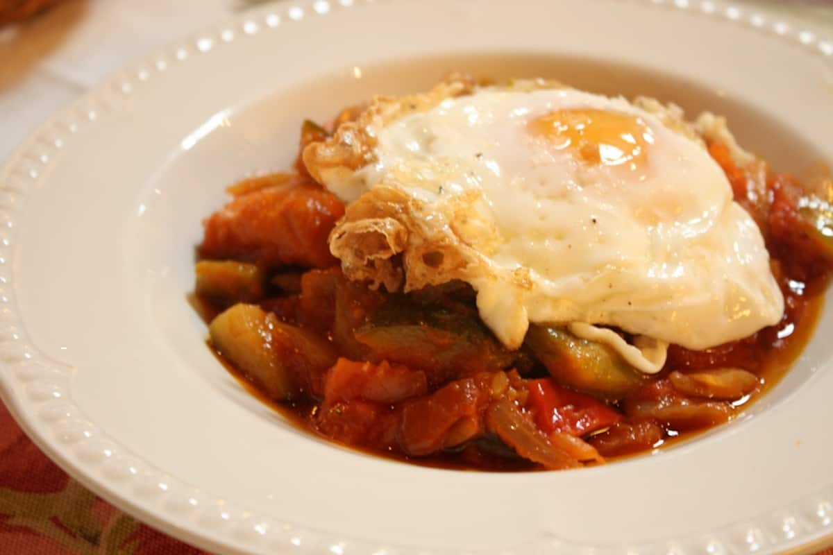 Dish of slow-simmered vegetables topped with a fried egg.