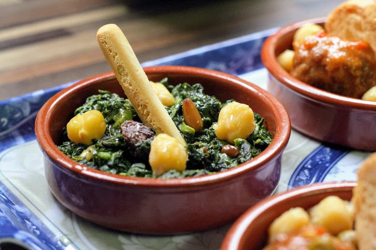 Small clay dish of sauteed spinach with raisins and toasted pine nuts, a traditional vegetarian tapas recipe.