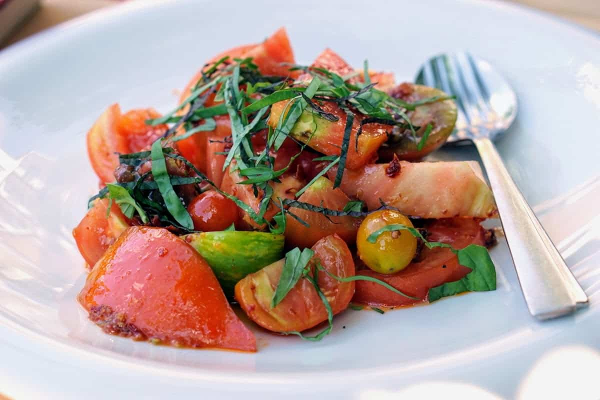 Plate of vegetarian tomato salad garnished with herbs.