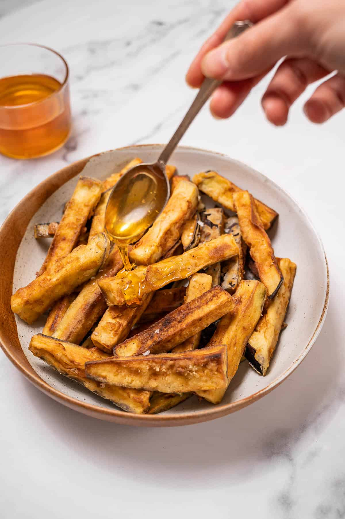 Fried eggplant with honey being drizzled on top