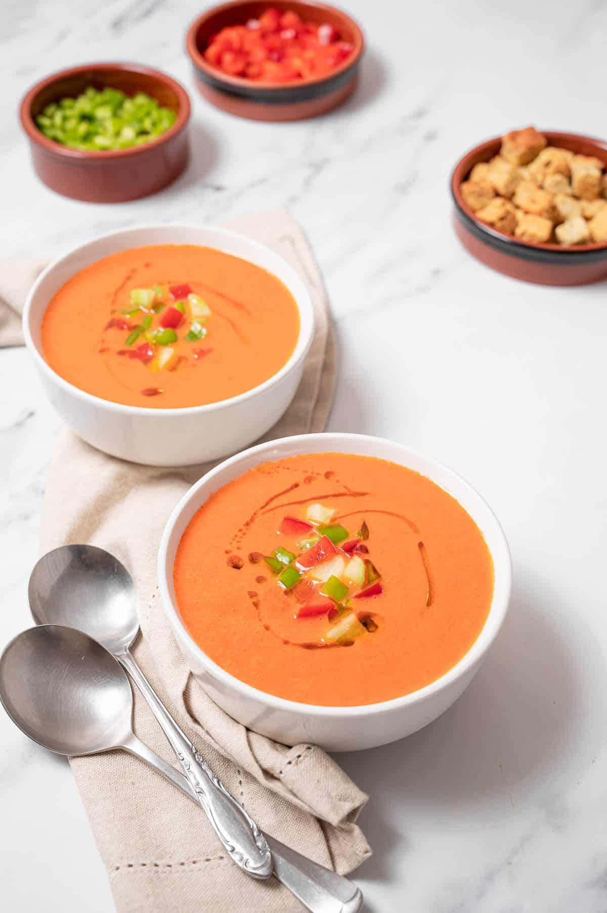 Two bowls of Spanish gazpacho with toppings. Diced pepper and croutons in clay bowls in the background.