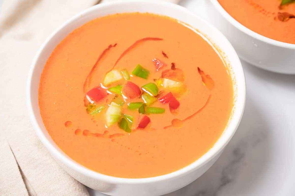 Close up bowl of gazpacho with diced veggie toppings.