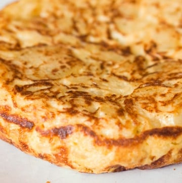 Finished Spanish omelet, the tortilla de patatas on a white plate.