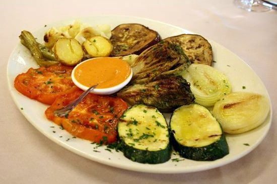 Roasted vegetables on a white plate with romesco sauce.