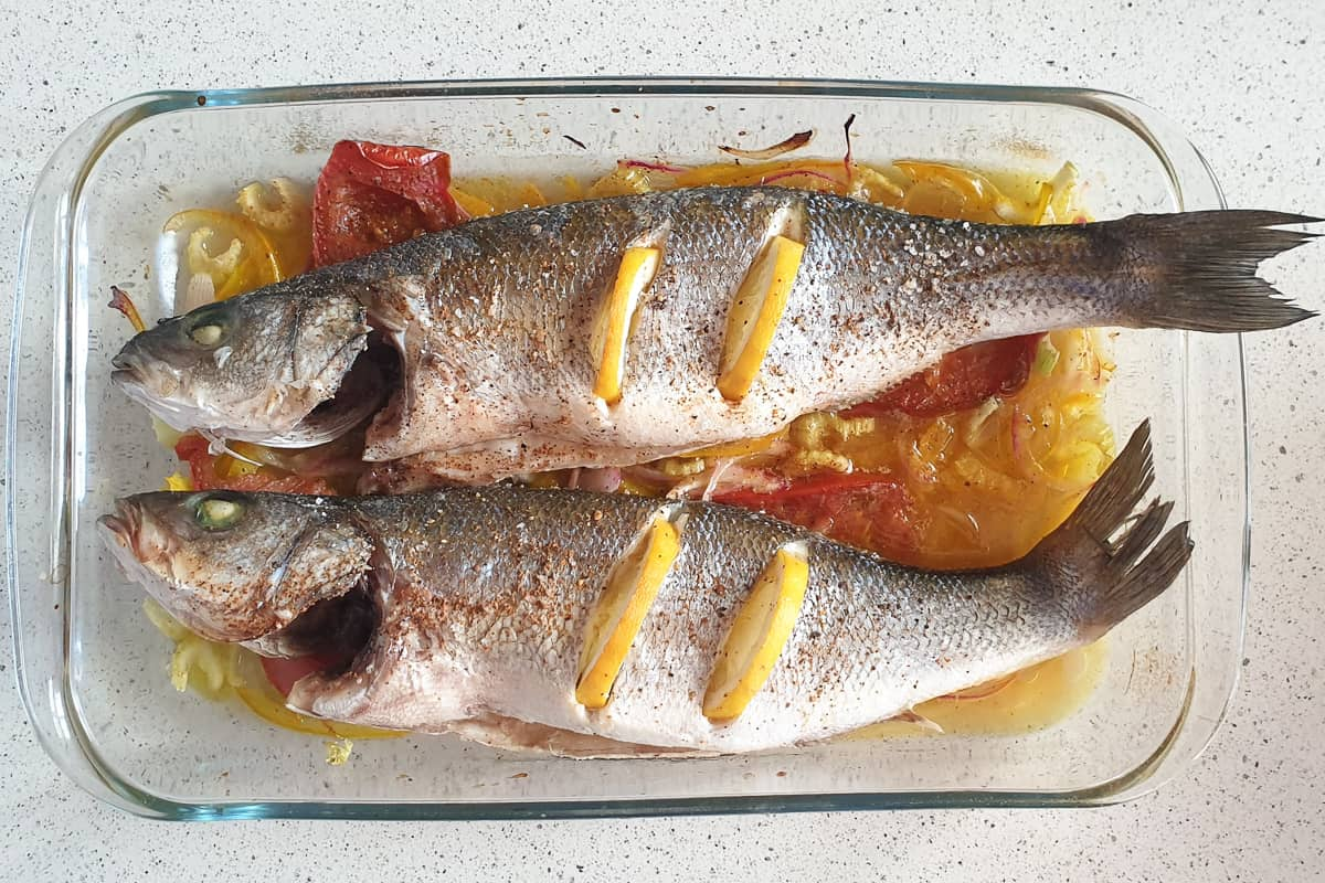 Two whole baked gilt head bream fish on a bed of onion and tomato in a clear serving dish