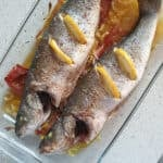 Baked gilt head bream in a clear serving dish with sliced lemons.