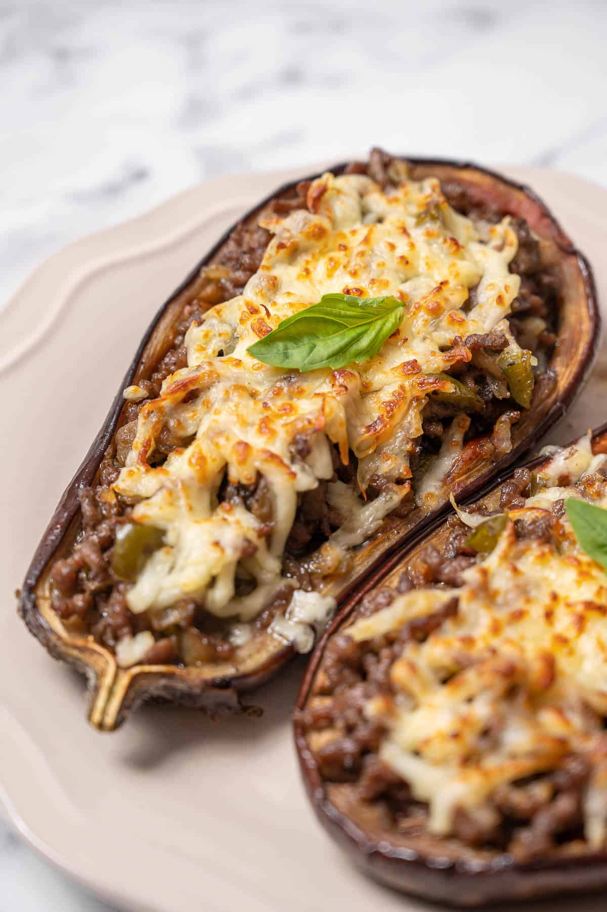 Berenjenas rellenas or Spanish stuffed eggplant on a white dish. Stuffed eggplant with meat and cheese.