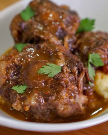 Rabo de toro in a white bowl served over mashed potatoes