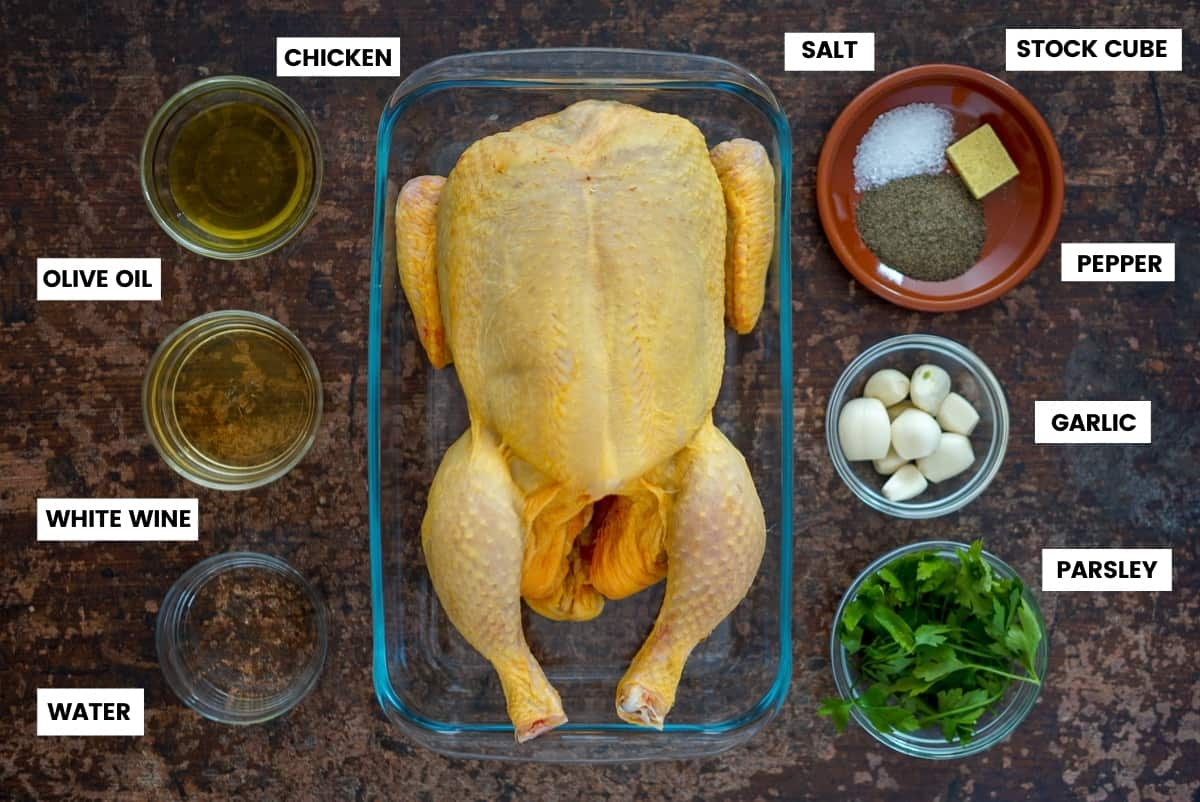 Overhead shot of ingredients for Spanish roast chicken. Olive oil, white wine, water, chicken, salt, pepper, stock cube, garlic, and parsley