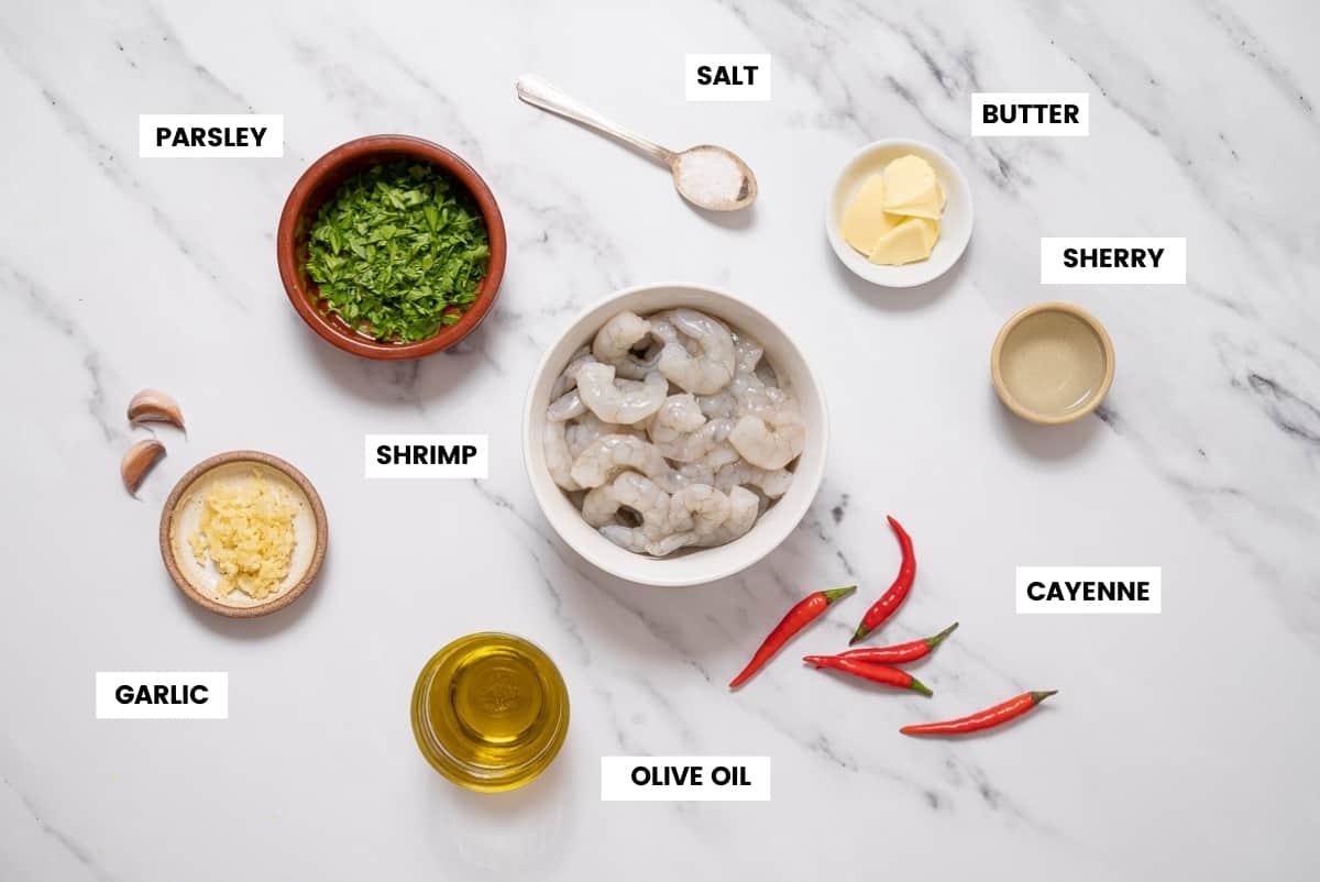 Ingredients to make Spanish garlic shrimp on a white marble countertop.