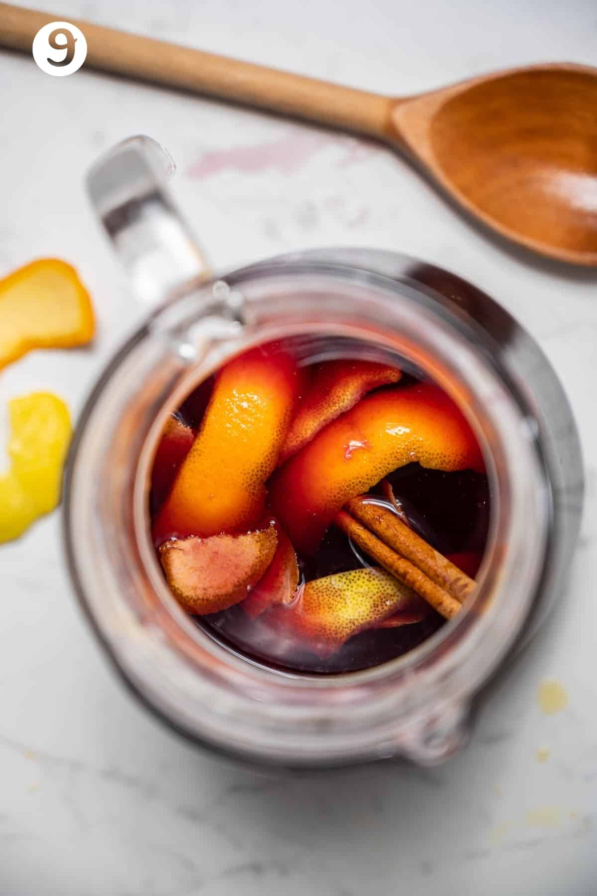 Overhead shot of a pitcher of red sangria with cinnamon stick, citrus peels, apple and nectarine.