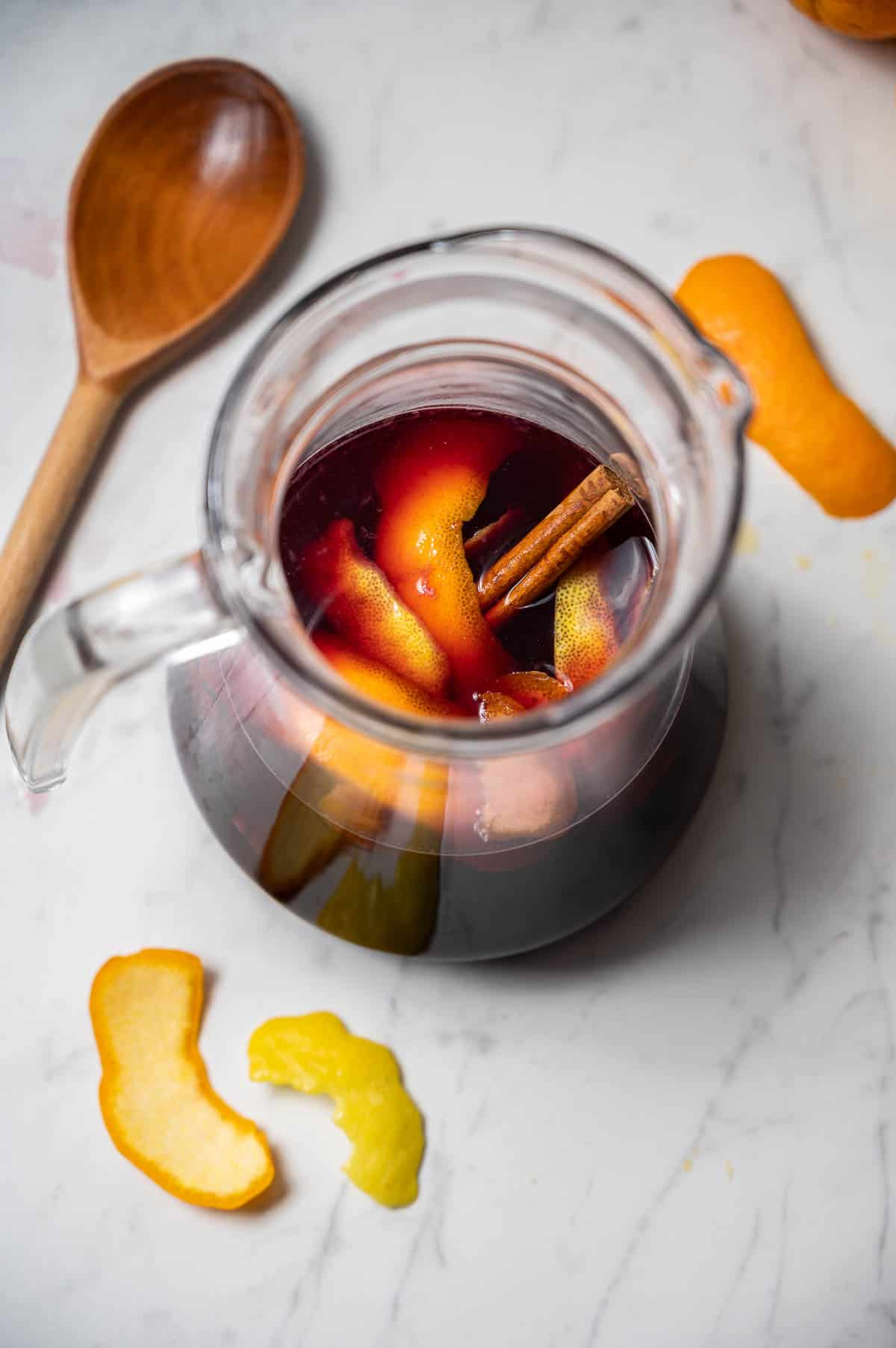 Pitcher of classic red sangria with citrus peel and cinnamon stick. A wooden spoon next to it.