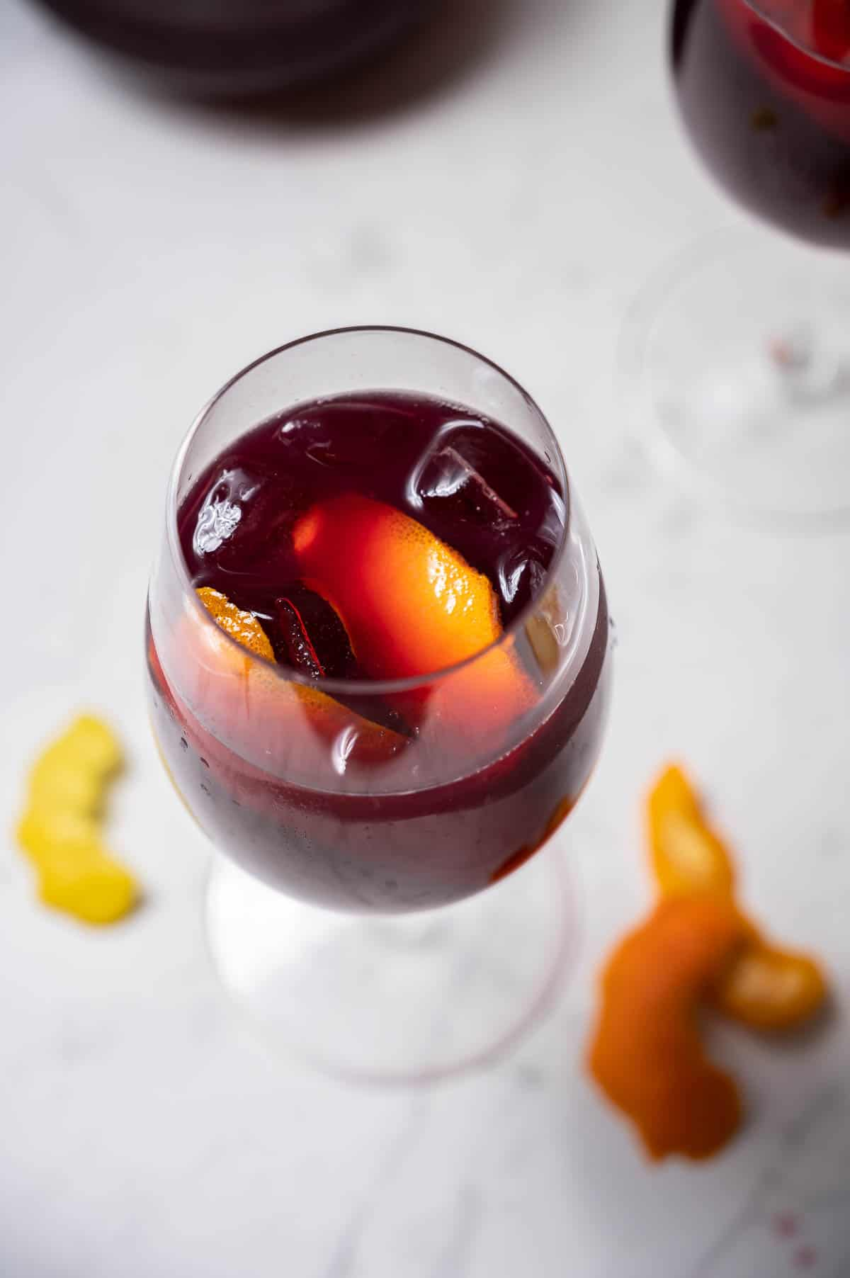 A glass of Spanish red sangria with citrus peel.