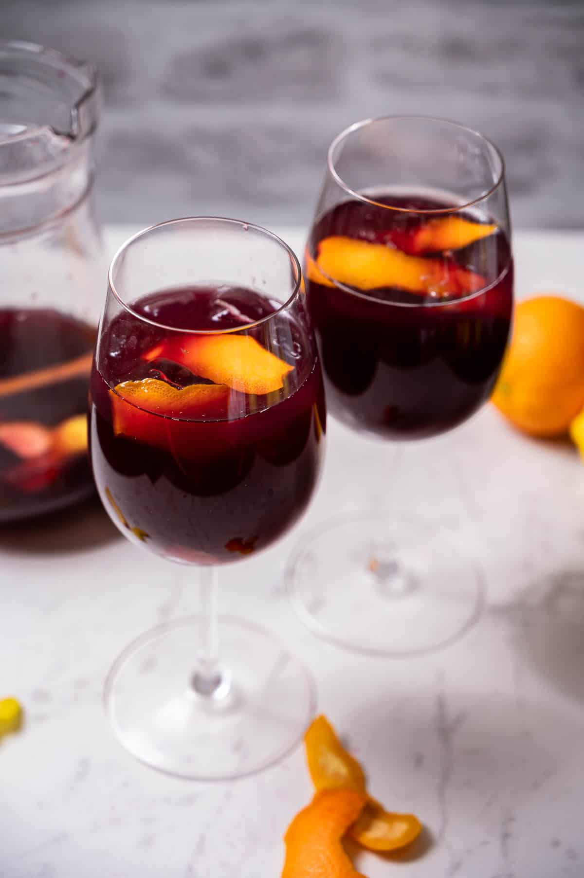 Two glasses of sangria garnished with citrus