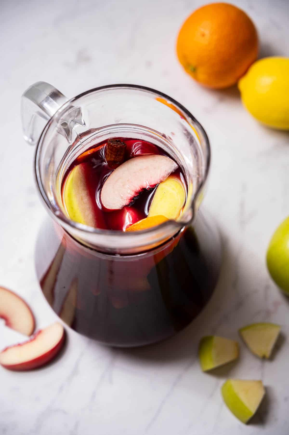 A pitcher of red wine sangria on a white countertop with fruit in the background