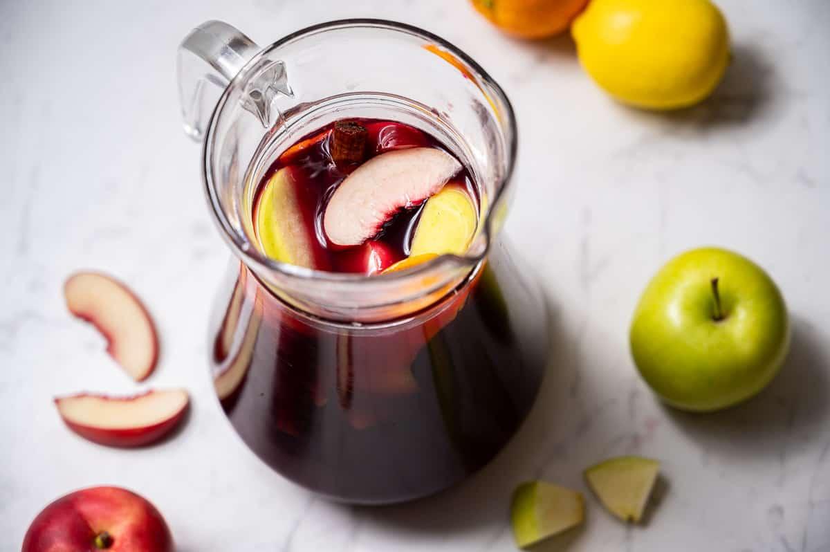 Pitcher of red wine sangria with apple, nectarine, lemon, and orange.