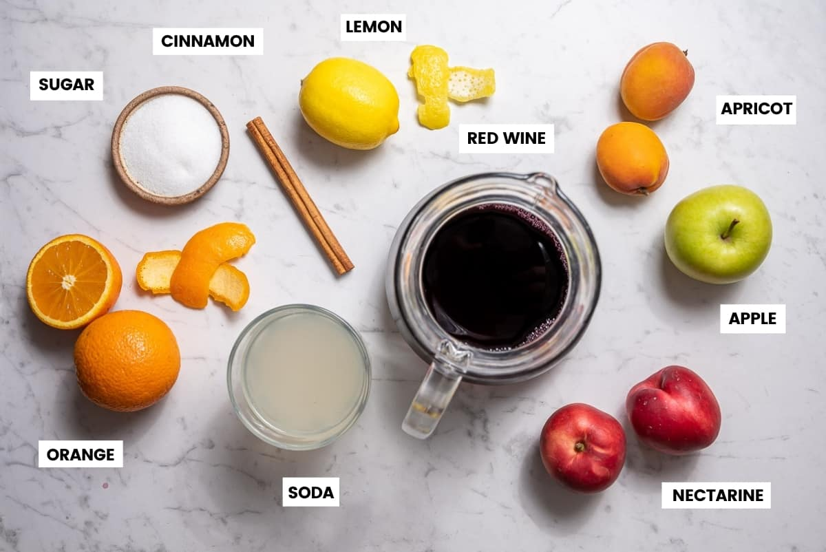 Ingredients for Spanish sangria laid out on a white countertop.