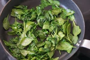 Fresh spinach wilting in a frying pan