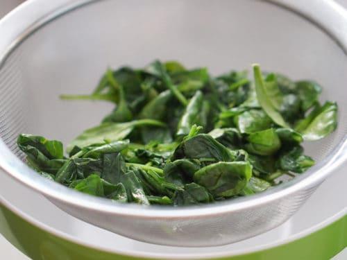 Spinach straining in a colander