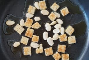 Cubed bread and almonds in a frying pan with olive oil