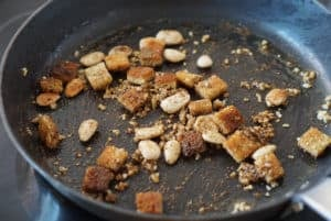 Sauteed bread cubes, garlic and almonds in a frying pan