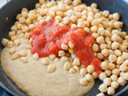 A frying pan with almond, garlic and bread paste next to garbanzo beans and tomato sauce