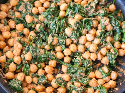 Seasoning the pan of spinach and chickpea stew with salt and pepper