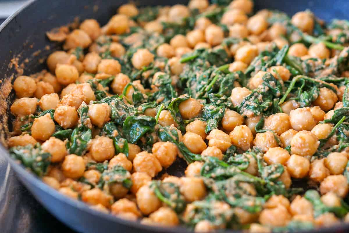 Spinach and chickpea stew in a frying pan on the stovetop.