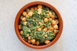 Spinach and chickpea stew in a clay dish