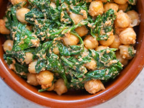 Close up of Spinach and chickpea stew in a clay dish