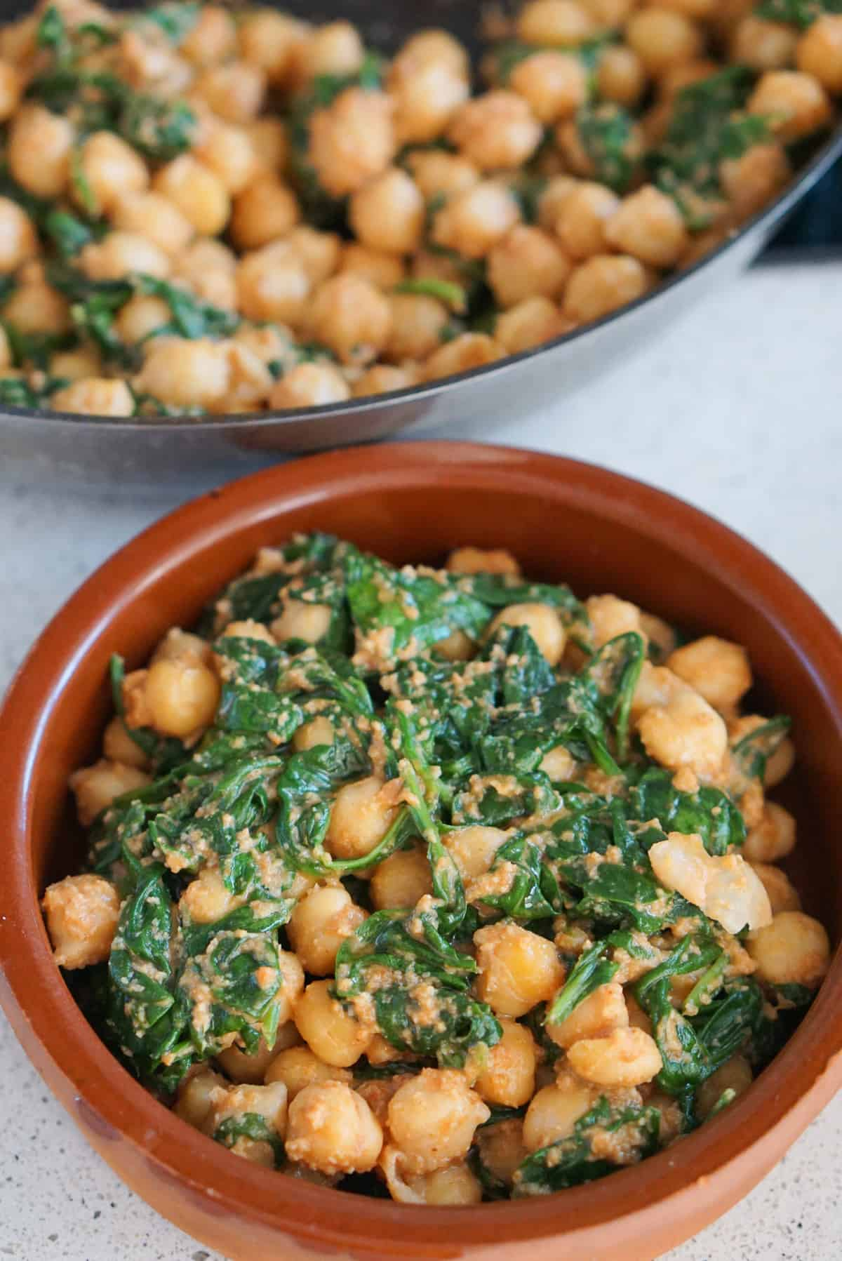 Spinach and chickpea stew in a clay dish in front of a pan full of more.