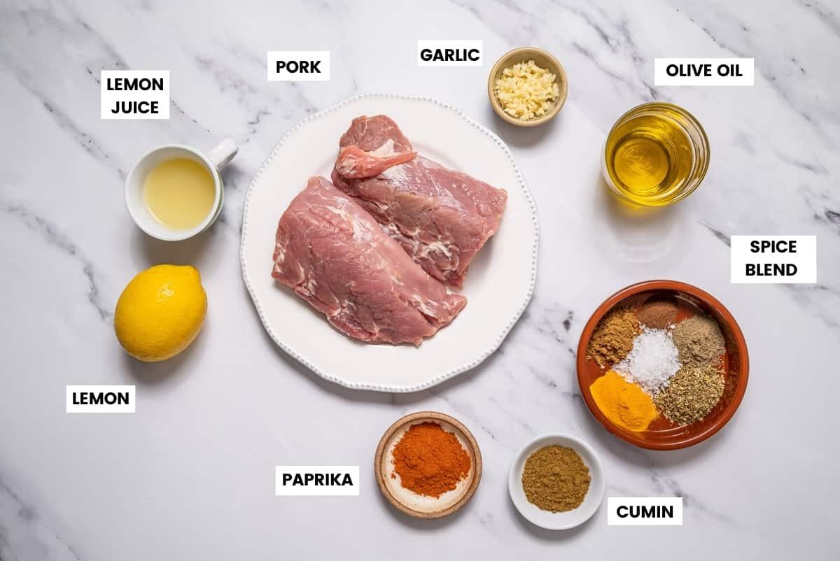 Spanish pork skewers ingredients on a marble countertop