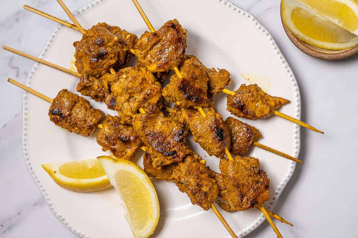 Spanish pork skewers on a white plate with lemon wedges.