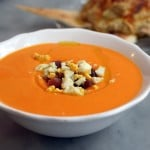 best salmorejo recipe in a white bowl topped with hard boiled egg and ham