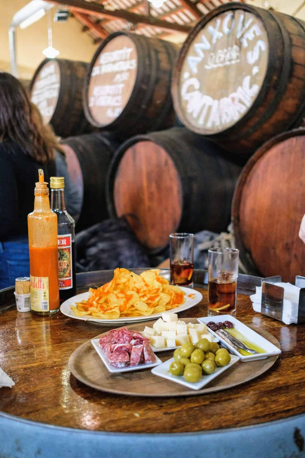 Aperitif tapas spread of cured meat, olives, cheese cubes, anchovies, potato chips, and vermouth set atop a wooden barrel.