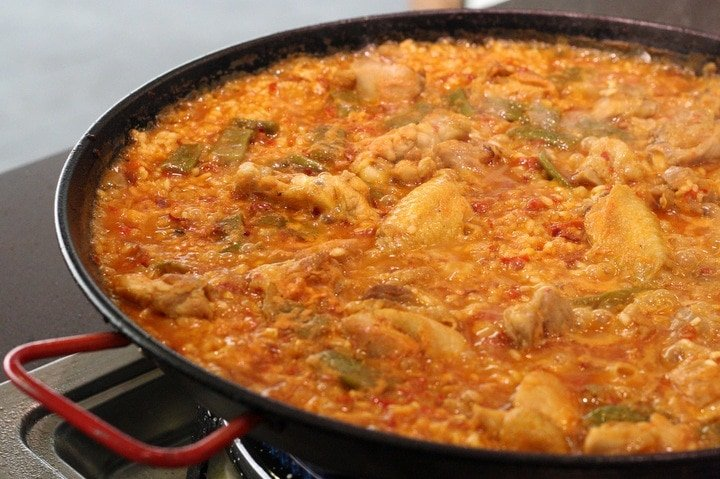 Traditional Spanish paella recipe for paella Valenciana. Rice with chicken and vegetables.